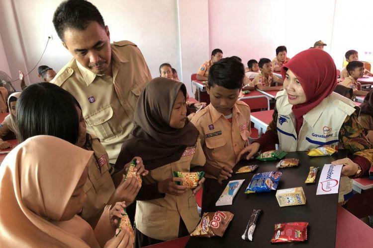 Dian Astriana, Corporate Communication Head Garuda Food (berkerudung merah) dan Herri Susanto Guru SD Kampung Sawah 02 (berseragam pramuka) mengajak siswa-siswi mempraktikkan cara membaca label pada kemasan produk Garuda Food.