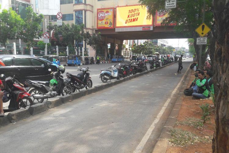 Sejumlah sepeda motor milik pengemudi ojek online diparkir di tepi separator jalur Transjakarta di Mangga Dua, Jakarta Utara, Mingu (15/4/2018)