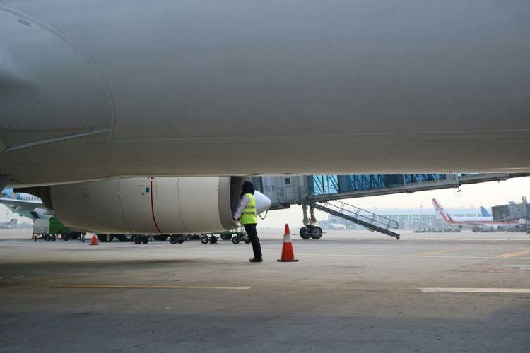 Staf teknisi perempuan Garuda Indonesia memeriksa bagian pesawat