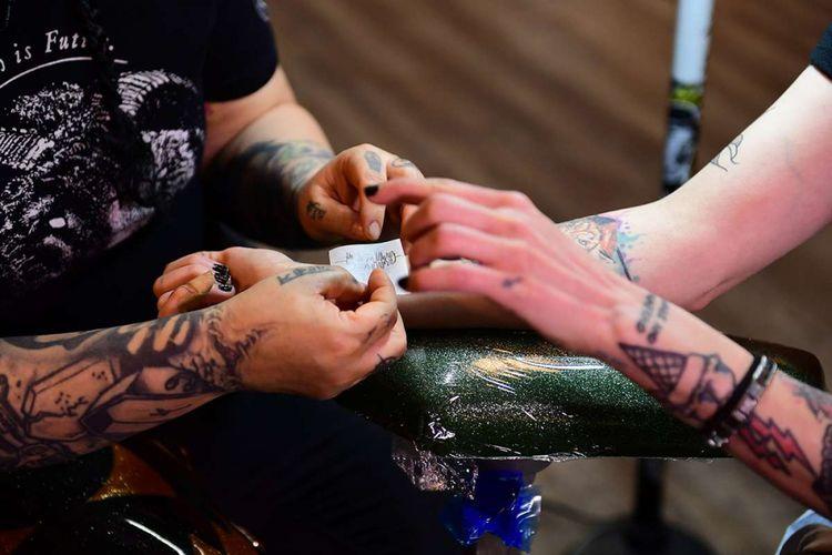 Seniman tato, Tiffany Garcia, menato pola gelombang suara di lengan konsumennya, Hanna Washlake, di Black Raven Tattoo di Torrance, California, Kamis (12/4/2018). Soundwave Tattoos yang diciptakan seniman Nate Siggard tengah menjadi tren di AS karena keunikannya yang bisa menghasilkan suara dengan bantuan aplikasi ponsel Skin Motion.