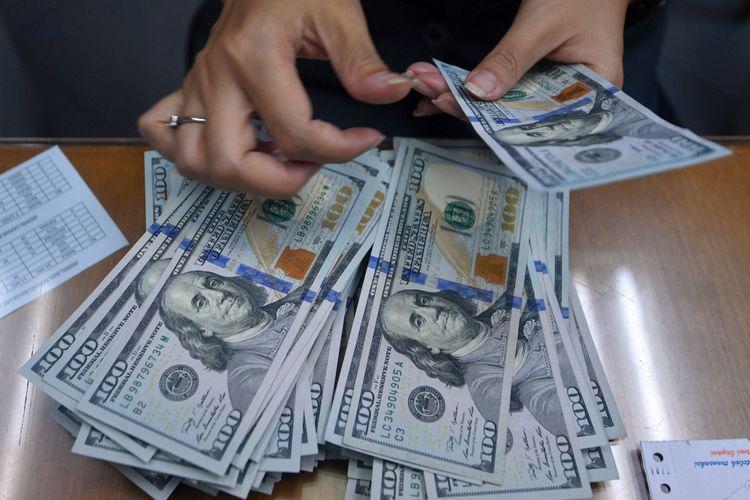 Petugas menghitung pecahan dolar Amerika di salah satu gerai penukaran mata uang di Kwitang, Jakarta Pusat, Selasa (8/5/2018). Nilai tukar rupiah terhadap dolla AS yang ditransaksikan pada Selasa (8/5/2018) ditutup melemah 51 poin atau 0,36 persen ke level Rp14.052 per dollar AS.