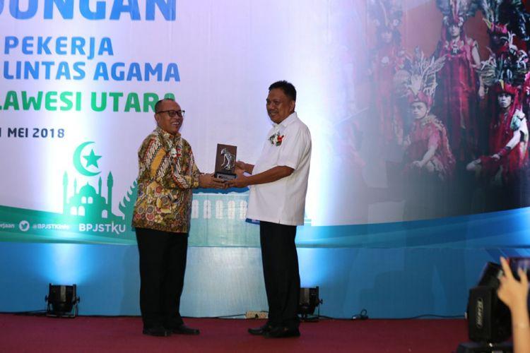 Direktur Utama BPJS Ketenagakerjaan, Agus Susanto (kiri) bersama Gubernur Sulawesi Utara, Olly Dondokambey (kanan). Pemerintah Provinsi Sulawesi Utara memecahkan rekor MURI pemberian jaminan sosial ketenagakerjaan untuk pekerja lintas agama terbanyak di Indonesia, Jumat (11/5/2018).