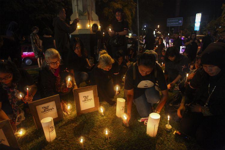 Warga menyalakan lilin dan berdoa bersama untuk korban bom gereja di Surabaya dalam aksi solidaritas di Solo, Jawa Tengah, Minggu (13/5/2018).