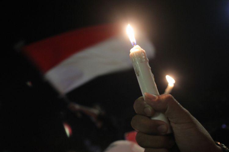 Warga menyalakan lilin saat aksi lilin kebersamaan Suroboyo Wani di Tugu Pahlawan, Surabaya, Jawa Timur, Minggu (13/5). Aksi yang diikuti ratusan orang dari berbagai lapisan itu mengecam aksi terorisme bom bunuh diri yang terjadi di Surabaya. ANTARA FOTO/Didik Suhartono/ama/18