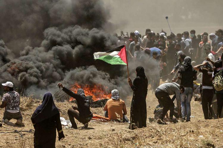 Seorang perempuan warga Palestina memegang bendera negaranya saat terjadi bentrokan dengan pasukan Israel di dekat perbatasan antara jalur Gaza dan Israel, di sebelah timur Kota Gaza, Senin (14/5/2018). Otoritas Palestina menyebut pasukan Israel telah menewaskan 55 orang dan melukai 2.700 orang dalam aksi protes dan bentrokan menentang pembukaan Kedutaan Besar Amerika Serikat di Yerusalem.