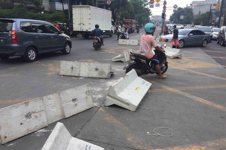 Puluhan warga dibantu pengendara yang melintas membongkar pembatas jalan di Simpang Duren Tiga, Kelurahan Duren Tiga, Kecamatan Pancoran, Jakarta Selatan, Sabtu (19/5/2018). Adapun pembatas jalan tersebut dipasang sebagai bagian uji coba penutupan simpang untuk memperlancar arus lalu lintas pasca-beroperasinya lintas bawah atau underpassMampang-Kuningan.