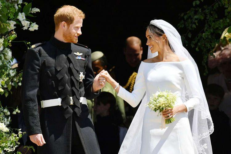 Pangeran Harry dan Meghan Markle meninggalkan Kapel St George di Kastil Windsor setelah pemberkatan pernikahan di Windsor, Inggris, Sabtu (19/5/2018). Sebanyak 600 tamu undangan menghadiri jamuan makan siang dan makan malam pada acara resepsi, ditambah 2.640 tamu dari warga biasa yang akan menimati teh dan kudapan di Istana Windsor.