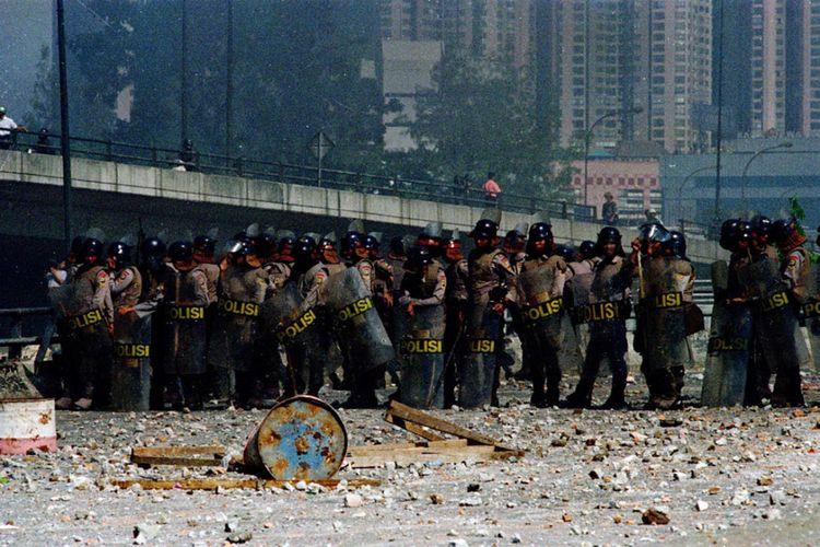 Anggota polisi berjaga setelah kerusuhan meletup di Simpang Grogol, Jakarta, 13 Mei 1998.
