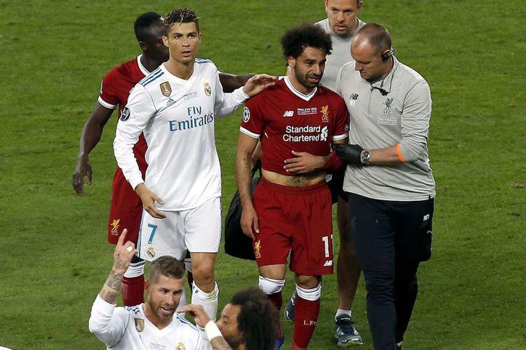 Pemain Real Madrid Cristiano Ronaldo (kiri) berjalan mendampingi pemain Liverpool Mohamed Salah yang mengalami cedera bahu saat laga final Liga Champions 2018 di Stadion NSK Olimpiyskiy di Kiev, Ukraina, Sabtu (26/5/2018) waktu setempat. Real Madrid meraih gelar juara Liga Champions 2018 seusai menang 3-1 atas Liverpool.