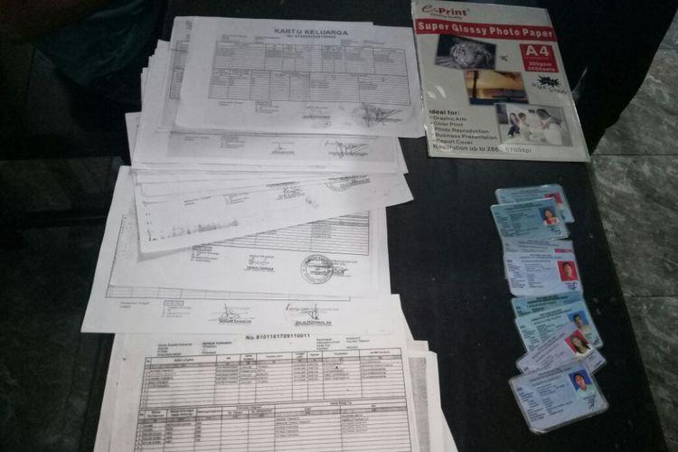 Sejumlah Kartu Keluarga dan KTP Palsu yang disita polisi dari rental pembuatan KTP Eketronik palsu di Desa Kairatu, kecamatan Kairatu Kabupaten Seram Bagian Barat, Maluku, Rabu (30/5/2018).