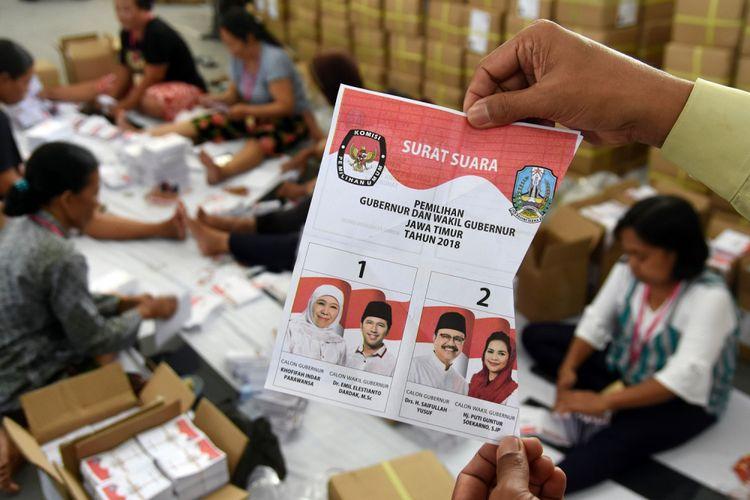 Petugas Komisi Pemilihan Umum (KPU) Surabaya menunjukkan kertas suara Pemilihan Kepala Daerah Jawa Timur 2018 yang rusak di Kantor Komisi Pemilihan Umum (KPU) Surabaya, Jawa Timur, Rabu (30/5). KPU Surabaya menyortir kertas suara Pilkada Jatim sebanyak 2.058.310 lembar kertas suara dengan melibatkan 30 orang  petugas. ANTARA FOTO/M Risyal Hidayat/aww/18.