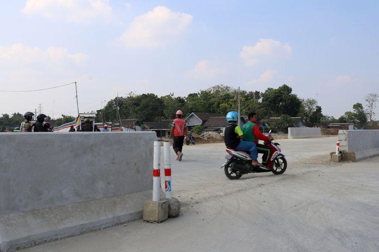 Warga melintas pada proyek tol Solo-Ngawi, Jawa Timur, Senin (4/6/2018). Terhitung mulai 8 Juni 2018 aatau H-7 Lebaran, Jalan tol fungsional tersebut sudah dapat dilalui pemudik.