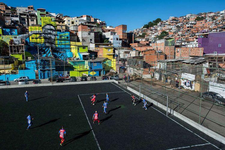 Foto diambil pada 20 Mei 2018, memperlihatkan warga bermain bola di lapangan dengan latar belakang gambar pemain sepak bola Brasil Gabriel Jesus yang dicat di dinding rumah-rumah di kawasan Perus, Brasil. Ada sejumlah lapangan sepak bola unik yang berdiri di berbagai penjuru dunia, mulai dari konstruksi bangunan hingga pemilihan lokasi yang tak biasa tempat dibangunnya stadion tersebut.