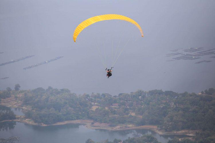 Anggota komunitas Paralayang Soloraya terbang di atas Waduk Gajah Mungkur, Jawa Tengah, Minggu (10/6/2018). Penerbang paralayang  yang lepas landas dari puncak bukit ini bisa menikmati keindahan Waduk Gajah Mungkur dan harus merogoh kocek sebesar Rp 400.000 per orang