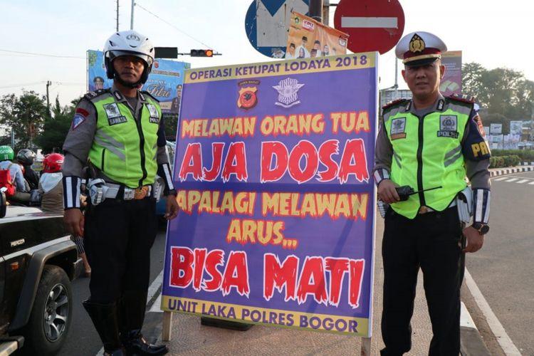 Polisi memasang spanduk imbauan dengan kata-kata nyeleneh yang ditujukan kepada pengendara jalan yang melintas di jalur Puncak, Bogor, Jawa Barat.