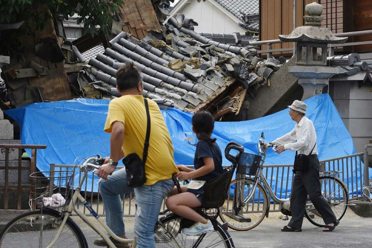 Warga Berhenti Untuk Melihat Kerusakan Pada Sebuah Rumah Yang Hancur Akibat Gempa Bumi Di Ibaraki