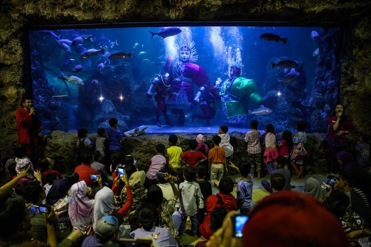 Dua penyelam sebagai tokoh Pitung memperagakan jurus-jurus silat di akuarium Seaworld, Taman Impian Jaya Ancol, Jakarta Utara, Jumat (22/6/2018). Pertunjukkan spesial yang bernama Ondel-ondel Underwater disiapkan Seaworld Ancol dalam rangka memeriahkan HUT DKI Jakarta yang memasuki usia ke-491.