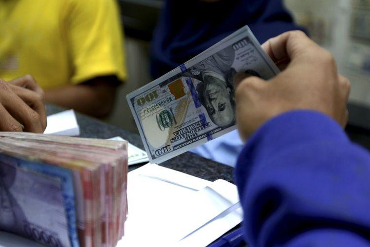Petugas menunjukan pecahan dollar Amerika di salah satu gerai penukaran mata uang di Kwitang, Jakarta, Jumat (29/6/2018). Nilai tukar rupiah terhadap dollar AS pada perdagangan Jumat (29/6/2018) siang berada pada level Rp 14.360.