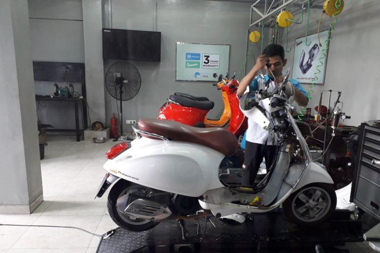 Salah seorang mekanik sedang melayani perbaikan salah satu unit Vespa di bengkel resmi Vespa di Jalan Margonda, Depok, Jumat (29/6/2018).