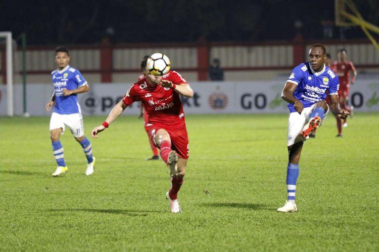 Pemain Persija Jakarta, Marko Simic (kiri) berebut bola dengan pemain Persib Bandung Victor Igbonefo pada laga liga 1 2018 di Stadion PTIK, Jakarta, Sabtu (30/6/2018). Persija berhasil menaklukan Persib dengan skor 1-0.