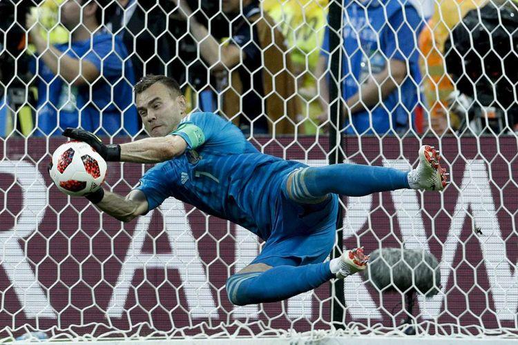 Kiper Russia Igor Akinfeev berhasil menangkap bola saat adu penalti pada laga 16 besar Piala Dunia 2018 melawan Spanyol di Stadion Luzhniki, Minggu (1/7/2018). Timnas Rusia lolos ke babak perempat final setelah menyingkirkan Spanyol lewat drama adu penalti dengan skor 4-3.