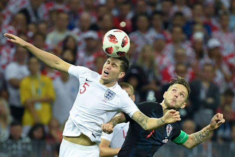 Pemain Kroasia Ivan Rakitic (kanan) beradu sundulan dengan pemain Inggris John Stones pada laga babak semifinal di Luzhniki Stadium, Rabu (11/7/2018) atau Kamis dini hari WIB. Kroasia melaju ke babak final Piala Dunia usai mengalahkan Inggris dengan skor 2-1.