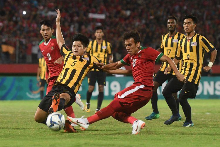 Pesepak bola Indonesia U-19 Egy Maulana Vikri (tengah) menendang bola yang dihalangi pesepak bola Malaysia U-19 Muhammad Anwar (kiri) dalam laga semifinal Piala AFF U-19 di Gelora Delta Sidoarjo, Sidoarjo, Jawa Timur, Kamis (12/7/2018). Indonesia kalah adu penalti dari Malaysia dengan skor 3-4.