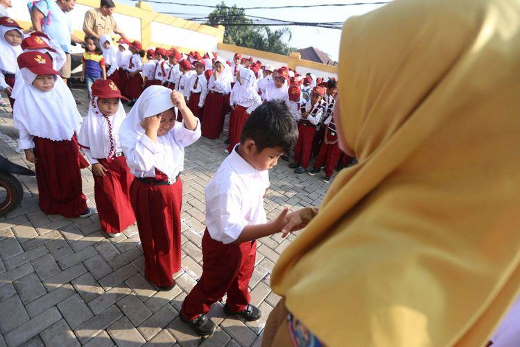 Guru bersalaman dengan murid baru kelas 1 saat hari pertama masuk sekolah, di SD Negeri Lengkong Wetan 1, Serpong Utara, Tangerang Selatan, Senin (16/7/2018). Sebanyak 120 murid baru di SDN Lengkong Wetan 1 nampak diantar oleh orangtua pada hari pertama tahun ajaran baru 2018/2019