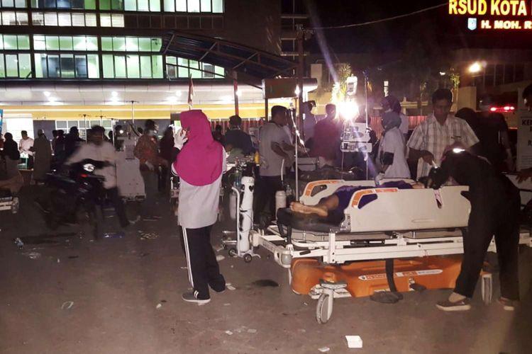 Petugas membawa pasien keluar dari rumah sakit saat terjadi gempa bermagnitudo 7 di Lombok, Nusa Tenggara Barat, Minggu (5/8/2018).