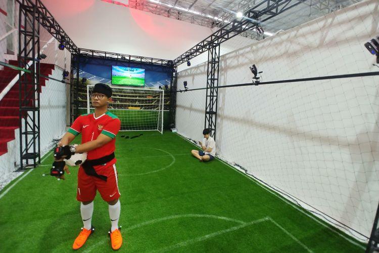 Game sepakbola adu penalti di mana kiper mengenakan headset VR mencoba menangkap bola yang ditendang pengunjung.