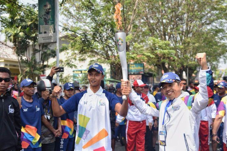 Ketua KONI Kabupaten Purwakarta Dedi Mulyadi saat menerima obor Asian Games dari seorang pelari di Purwakarta, Jawa Barat, Jumat (10/8/2018).