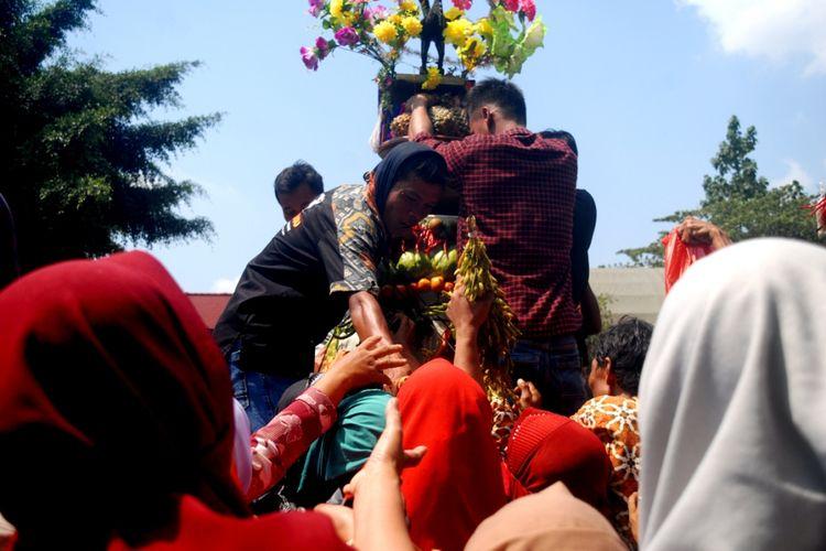 Warga Desa Sumber Jatipohon, Kecamatan Grobogan, Kabupaten Grobogan, Jawa Tengah berebut Gunungan setinggi 2,5 meter dalam tradisi sedekah bumi di obyek wisata Jatipohon, Grobogan, Kamis (9/8/2018).