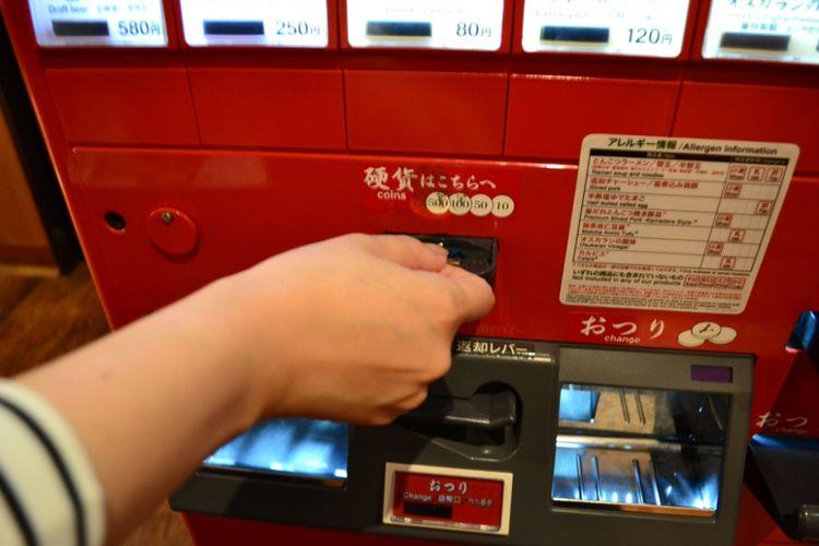 Uang koin dimasukan di lubang tengah.