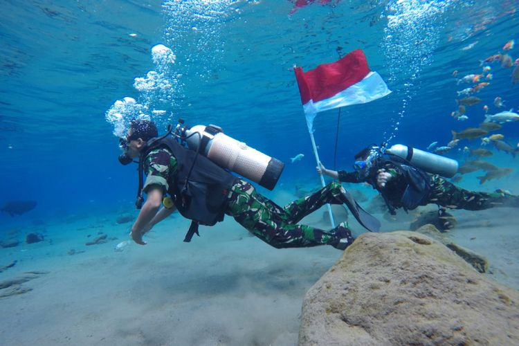 Anggota TNI Kodim Klaten mengibarkan bendera merah putih di dalam air di Umbul Ponggok, Klaten, Jawa Tengah.