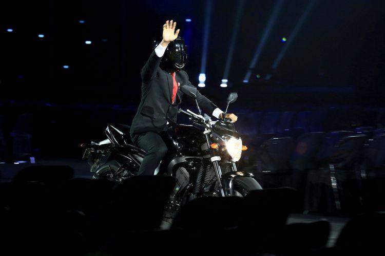 Presiden Joko Widodo mengendarai sepeda motor pada Upacara Pembukaan Asian Games ke-18 Tahun 2018 di Stadion Utama Gelora Bung Karno, Senayan, Jakarta, Sabtu (18/8/2018).