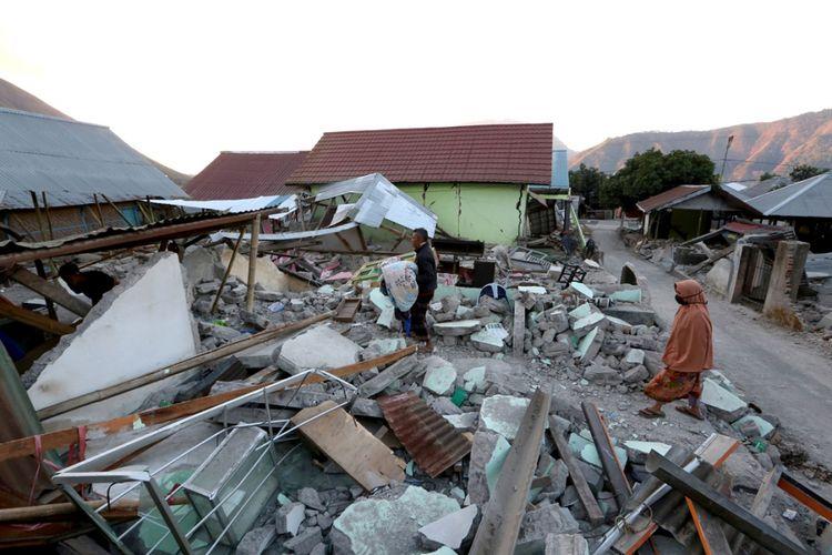 Warga memeriksa rumah mereka yang roboh di desa Sembalun, pulau Lombok pada 20 Agustus 2018 setelah serangkaian gempa bumi dicatat oleh seismolog sepanjang 19 Agustus. Menurut laporan pihak berwenang pada Senin (20/8/2018), setidaknya 10 orang tewas setelah serangkaian gempa kuat mengguncang pulau Lombok. Ini merupakan gempa baru yang berbeda dari gempa berkekuatan M 7,0 pada Minggu (5/8/2018) yang telah menewaskan ratusan nyawa dan ribuan orang kehilangan tempat tinggal.