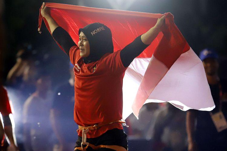 Atlet panjat tebing Indonesia Aries Susanti Rahayu mengibarkan Bendera Merah Putih setelah berhasil meraih medali emas pada kategori speed Asian Games 2018 di Arena Panjat Tebing Jakabaring Sport City, Palembang, Sumatera Selatan, Kamis (23/8/2018).