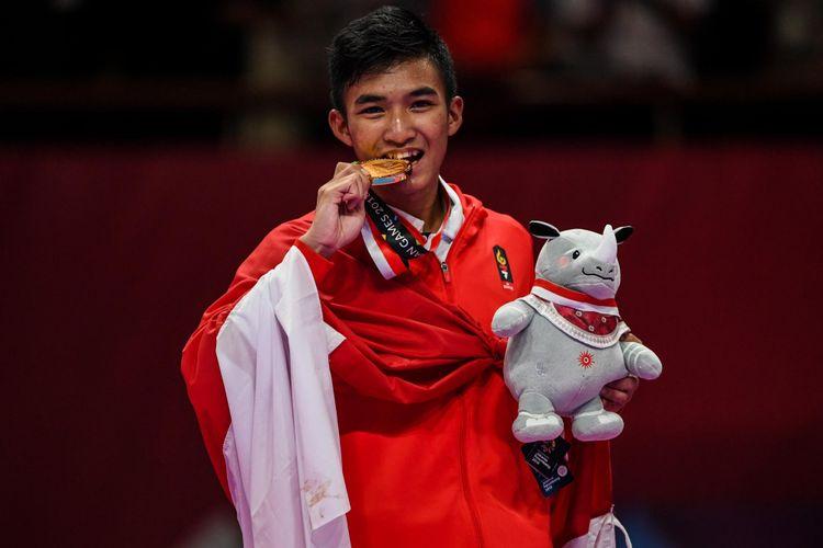 Karateka Indonesia, Rifki Ardiansyah Arrosyiid saat menerima medali dalam final Putra -60kg di Gedung JCC Plenary Hall, Jakarta Pusat, Minggu (26/8/2018). Rifki Ardiansyah Arrosyiid menang atas karateka Iran, Mahdi Zadeh Amir dengan skor 9-7 dan meraih medali Emas.