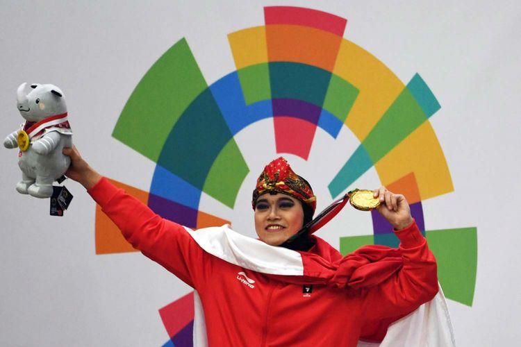 Pesilat Indonesia peraih medali emas Puspa Arumsari berpose usai upacara penyerahan medali nomor tunggal putri pencak silat seni Asian Games 2018 di Padepokan Pencak Silat Taman Mini Indonesia Indah (TMII), Jakarta, Senin (27/8/2018).