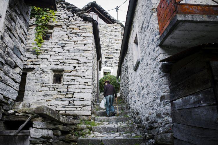 Seorang penduduk Corippo berjlan di antara rumah-rumah kosong di desa.