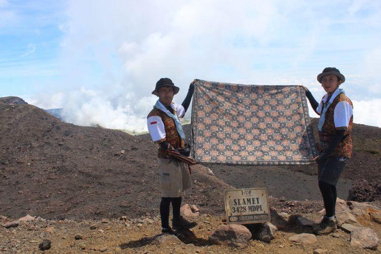 Siswanto dan Sultan sedang membentangkan kain batik di puncak Gunung Slamet pada Jumat (7/9/2018).