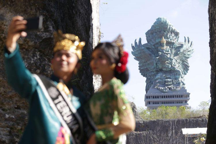 Sejumlah pengunjung berswafoto dengan latar belakang Patung Garuda Wisnu Kencana (GWK) usai diresmikan di Kuta Selatan, Bali, Sabtu (22/09/2018). Patung setinggi 121 meter dengan lebar 64 meter tersebut resmi diresmikan dan menjadi patung tertinggi ketiga di dunia.