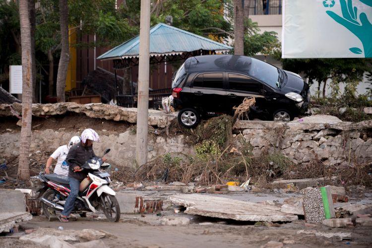 Seorang pria berusaha mengendarai sepeda motornya melalui lumpur di Pal, Sulawesi Tengah, Sabtu (29/9/2018), setelah gempa kuat dan tsunami melanda daerah tersebut. Hampir 400 orang tewas akibat gempa dan tsunami di Sulawesi Tengah, Jumat (28/9/2018).