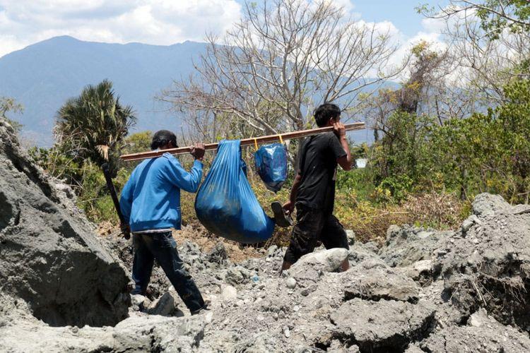 Dua orang warga Petobo mengevakuasi harta benda yang bisa diselamatkan setelah lumpur menggelamkan permukiman mereka