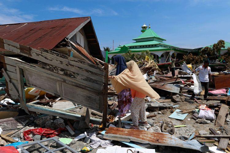 Warga membersihkan pling bangunan rumah yang roboh akibat gempa dan tsunami di Wani 2, Kecamatan Tanatopea, Kabupaten Donggala, Sulawesi Tengah, Selasa (2/10/2018). Gempa yang terjadi di Palu dan Donggala mengakibatkan 925 orang meninggal dunia dan 65.733 bangunan rusak.