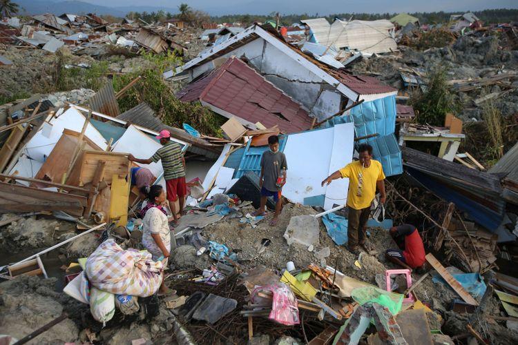 Warga korban gempa bumi menyelamatkan barang berharga yang masih bisa digunakan di Petobo, Palu, Sulawesi Tengah, Jumat (5/10/2018). Petobo menjadi salah satu wilayah yang paling parah terdampak gempa karena dilalui sesar Palu Koro.