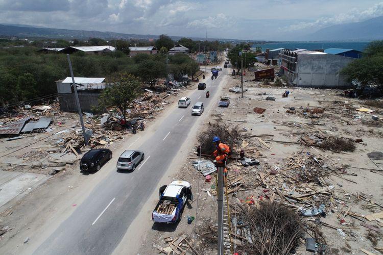 Petugas memperbaiki jaringan listrik di Jalan Trans Sulawesi di Mamboro, Kecamatan Palu Utara, Palu, Sulawesi Tengah, yang putus akibat gempa dan tsunami, Sabtu (6/10/2018). Jaringan listrik di beberapa wilayah di Kota Palu sudah mulai menyala.