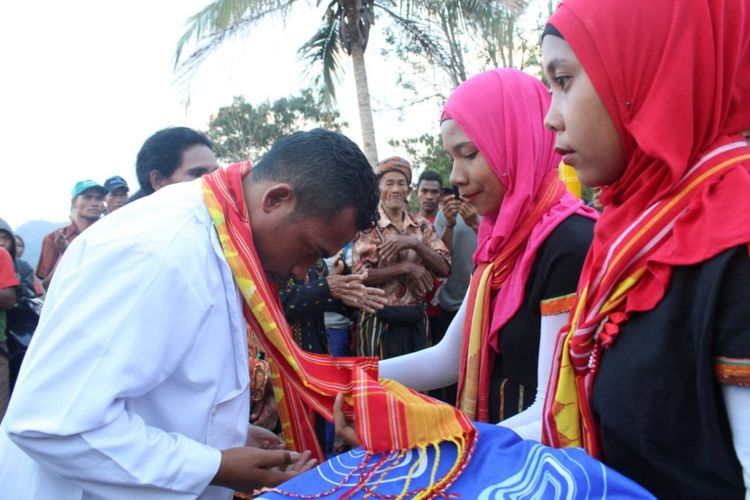 Dua perempuan muslim mengalungkan selendang congkar kepada Imam Katolik, Pastor Rikardus Karno, Projo di Kampung Toleransi Puncak Liur, Desa Ranamese, Kecamatan Sambirampas, Kabupaten Manggarai Timur, Flores, Nusa Tenggara Timur.