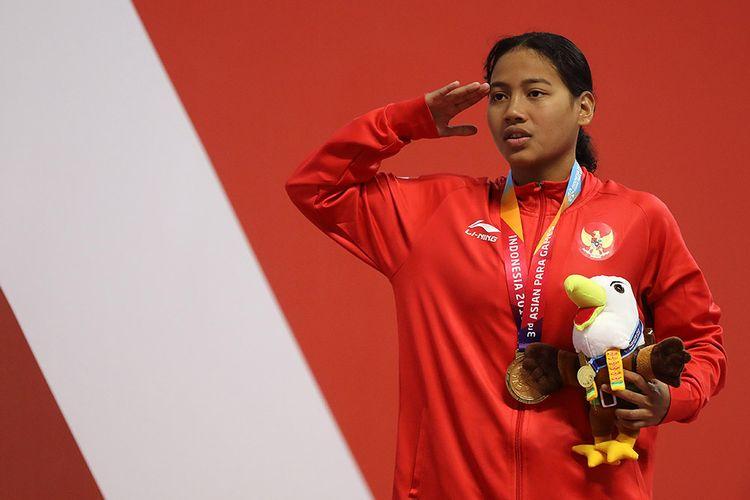 Perenang Indonesia Syuci Indriani menyanyikan Indonesia Raya usai beraksi di nomor 100 meter gaya dada putri SB 14 di Gelora Bung Karno Aquatic Center, Senayan, Jakarta, Senin (8/10). Syuci berhasil meraih medali emas dengan catatan waktu 1 menit 23,95 detik.
