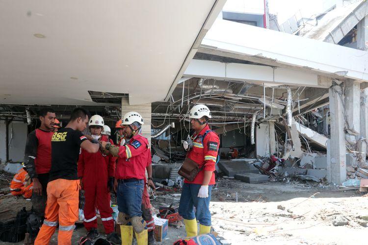 Sejumlah anggota Basarnas sedang mendiskusikan cara mengeluarkan seorang jenazah di reruntuhan Hotel Mercure, Palu. Posisi jenazah tertimpa 3 beton di sebuah ruangan.